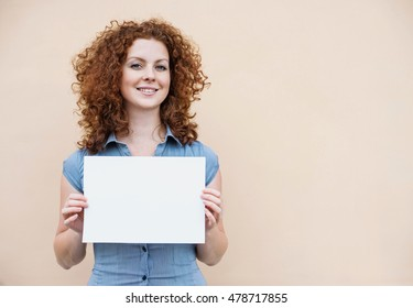 Happy young woman holding blank white banner