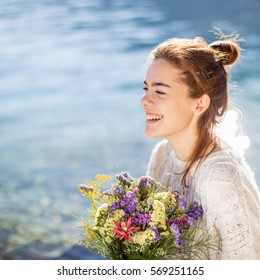 A happy young woman holding bouquet. Sea background