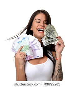 Happy young woman holding up cash money five one fifty hundred euro in one hand and dollars in other compare thinking looking at the corner isolated on a white background