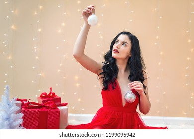 Happy young woman holding Christmas baubles on a shiny light background