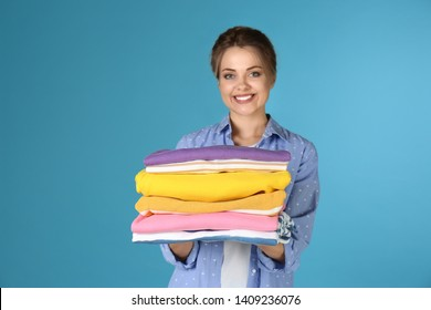 Happy young woman holding clean laundry on color background