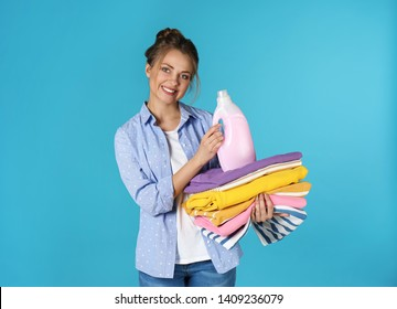 Happy young woman holding clean clothes and laundry detergent on color background