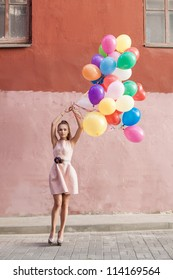 Happy young woman holding colorful balloons on a street - outdoors