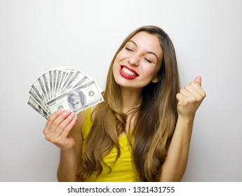Happy young woman holding dollar currency satisfied