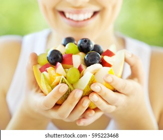 Happy young woman holding fresh fruits served in melon bowl as dessert