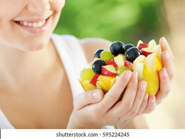 Happy young woman holding fresh fruits served in melon bowl as dessert. Focus on melon
