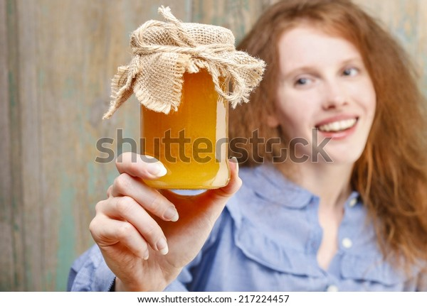 Happy young woman holding glass jar of honey, copy space