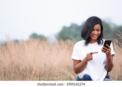 happy young woman holding her phone and credit card