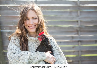 Happy young woman holding his chicken in the backyard. Happy country life concept