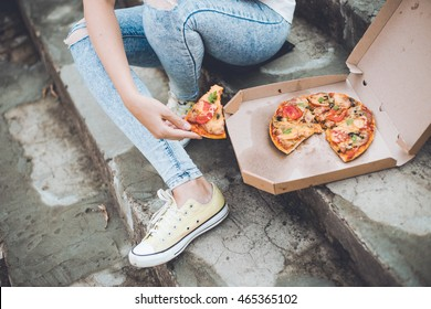 Happy Young woman holding hot pizza in box, seat outdoor in european street