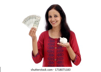 Happy young woman holding Indian currency notes and piggy bank