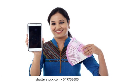 Happy young woman holding Indian currency and mobile phone