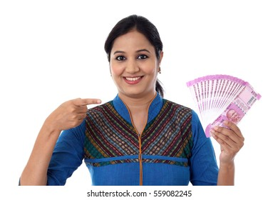 Happy young woman holding Indian 2000 rupee notes