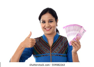 Happy young woman holding Indian 2000 rupee notes and making thumb up gesture