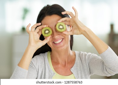 happy young woman holding kiwi in front of eyes