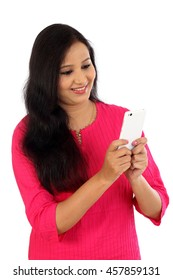 Happy young woman holding mobile phone and texting