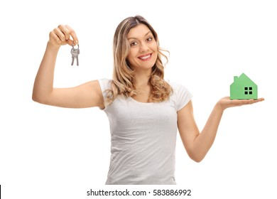 Happy young woman holding a pair of keys and a model house isolated on white background