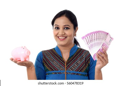 Happy young woman holding a piggy bank and Indian rupee notes-Money savings concept