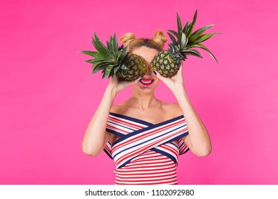 Happy young woman holding a pineapple on a pink background. Summer, diet and holidays concept