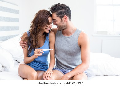 Happy young woman holding pregnancy test sitting besides husband in room
