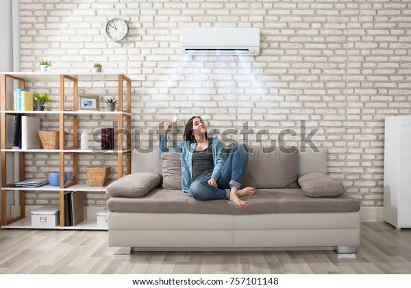 Joven feliz sosteniendo el control remoto relajándose bajo el aire acondicionado