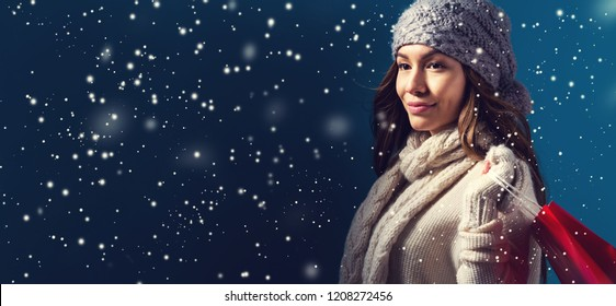 Happy young woman holding a shopping bag in a snowy night