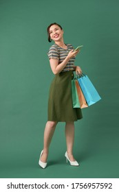 happy young woman holding shopping bags and mobile phone over green background