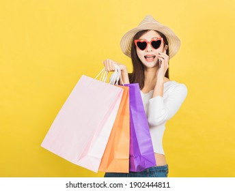 happy young woman holding shopping bags and talking on mobile phone