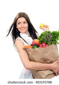 Happy young woman holding a shopping bag full of groceries fruits and vegetables holding lemon isolated on a white background