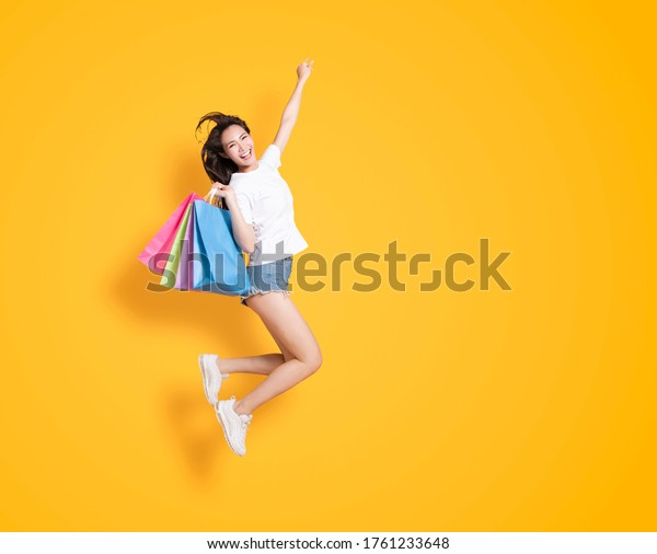 happy young woman holding with shopping bags and jumping
