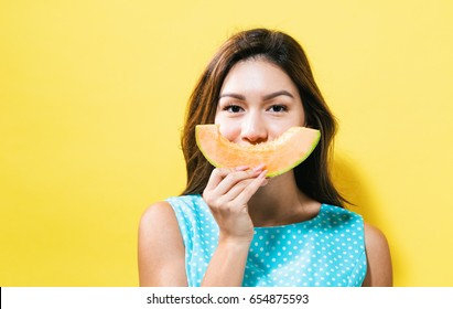 Happy young woman holding a slice of cantaloupe on a yellow background