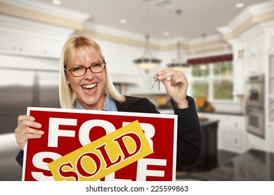 Happy Young Woman Holding Sold For Sale Real Estate Sign and Keys Inside Beautiful Custom Kitchen.