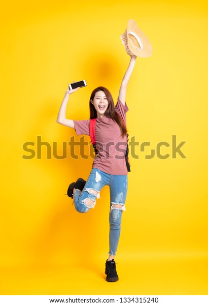 happy young woman holding summer hat and showing smart phone