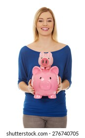 Happy young woman holding two piggybanks.
