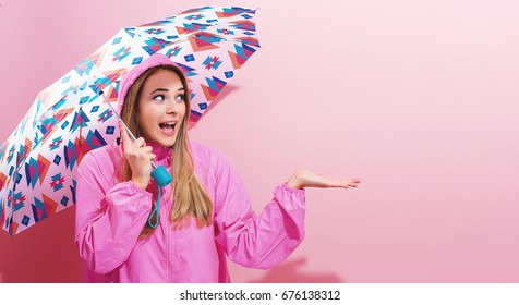 Happy young woman holding an umbrella on a pink background