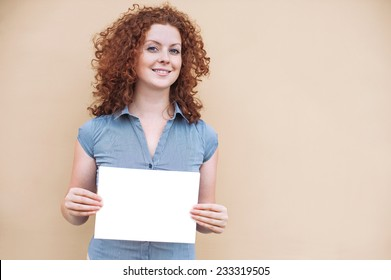 Happy young woman holding a white banner