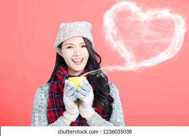 happy young woman  holds a cup with hot coffee or tea
