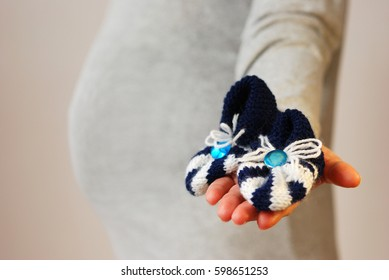Happy young woman holds shoes of future baby against background of her belly on last month of pregnancy out of focus