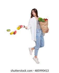 Happy young woman holds shopping paper bag full of groceries, vegetables and fruits and throw away glazed donuts, isolated at white background. Healthy food shopping choice. Female buyer