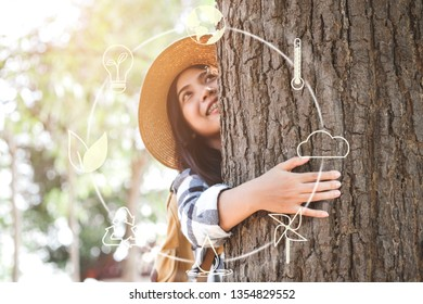 Happy young woman hug a big tree with icons about environment on image , Concept of environmental conservation and protection of our world sustainable.
