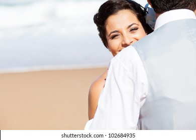 happy young woman hugging husband on beach