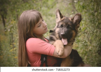 Happy Young Woman hugs beautiful fluffy German Shepherd dog puppy in the park