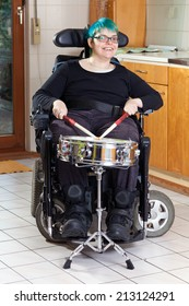 Happy young woman with infantile cerebral palsy due to birth complications confined to a multifunctional wheelchair beating on a drum as part of her therapy smiling at the camera
