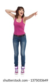Happy young woman in jeans, magenta tank top and sneakers is standing, looking away, pointing and shouting. Front view. Full length studio shot isolated on white.