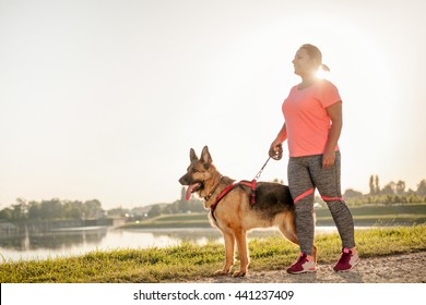 Happy young woman jogging with her German Shepherd Dog