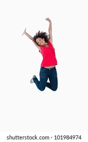 Happy young woman jumping in the air against a white background