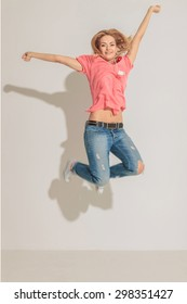 Happy young woman jumping with both hands in the air