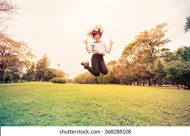 Happy young woman jumping high on the park