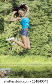 Happy young woman jumping for joy in a summer park