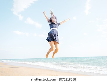 Happy young woman jumping on sand beach near the sea, summer vacations.